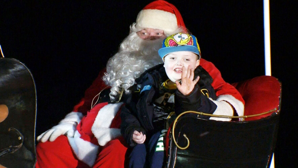 Evan had a wide smile as he rode off in a sleigh with Jolly Old Saint Nick, who was part of the 25-float procession.
