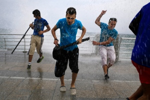 Lebanese men try to avoid getting soaked by high waves crashing on the seafront at the Corniche, or waterfront promenade, in Beirut, Lebanon, Sunday, Oct. 25, 2015. (AP/Hassan Ammar)