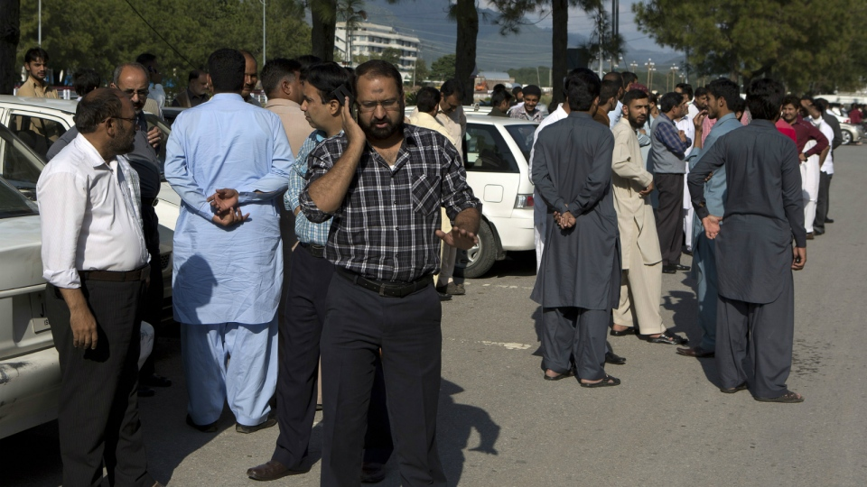 People stand outside their offices after a severe earthquake is felt in Islamabad, Pakistan on Monday, Oct. 26, 2015. (AP / B.K. Bangash)