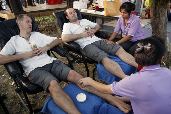 Tourists from the Netherlands receive a massage as they wait along with thousands of others for a flight out of Thailand, at the U-Tapao airport, some 160 kilometers south of Bangkok, Monday, Dec. 1, 2008. (AP / Ed Wray)