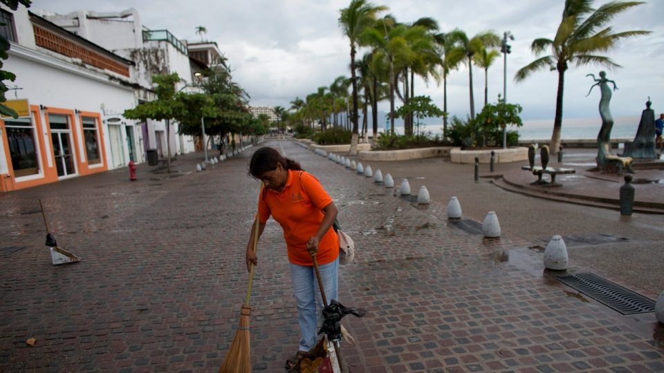 A city cleaner sweeps normal leaves and debris from a seafront walkway, the morning after Hurricane Patricia passed further south sparing Puerto Vallarta, Mexico, Saturday, Oct. 24, 2015. (AP / Rebecca Blackwell)