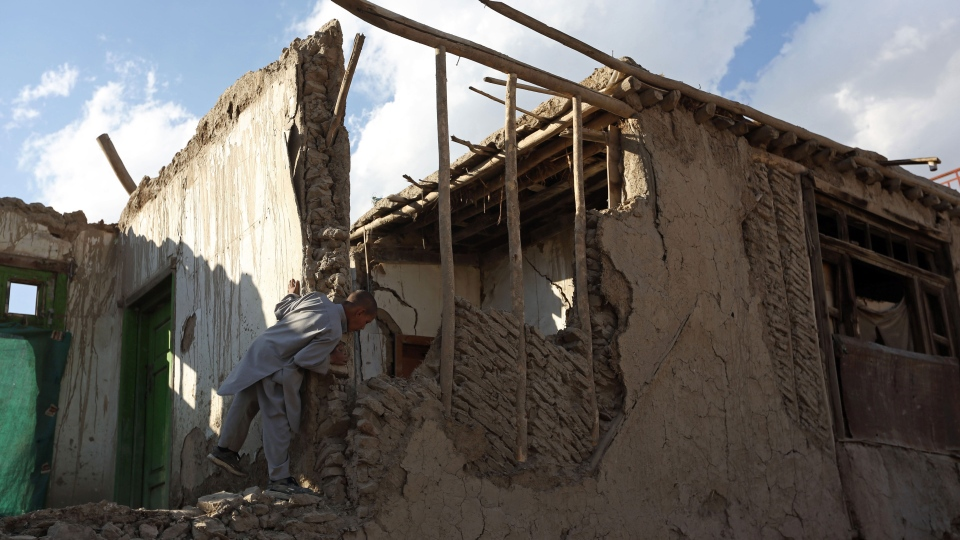An Afghan boy looks at a damaged house following an earthquake, in Kabul, Afghanistan, Monday, Oct. 26, 2015.  (AP / Rahmat Gul)