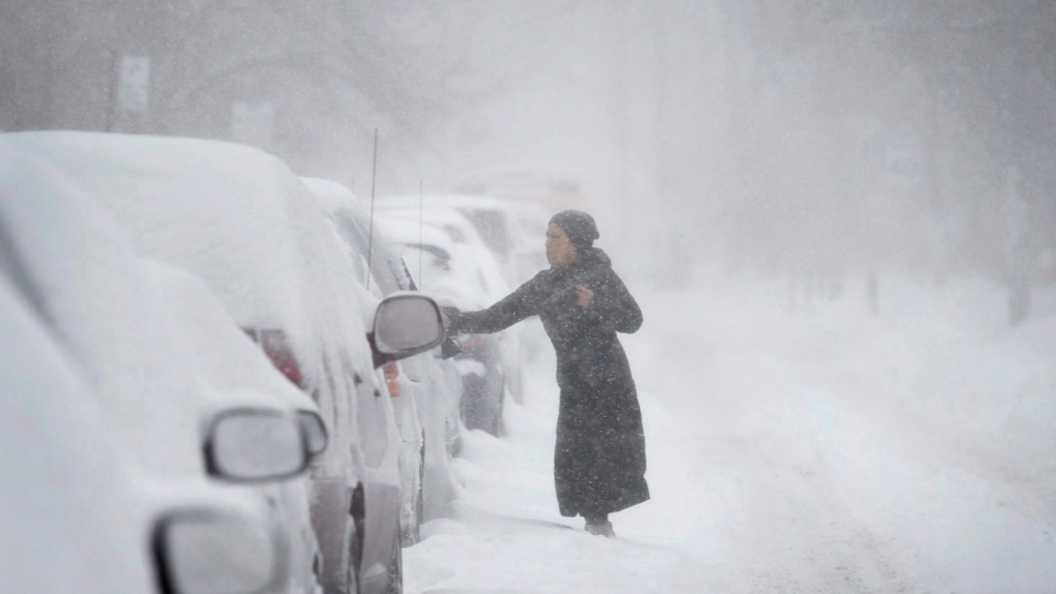 A woman clears snow from a vehicle during a winter storm, Monday, Feb. 2, 2015, in Toronto. (Darren Calabrese / The Canadian Press)