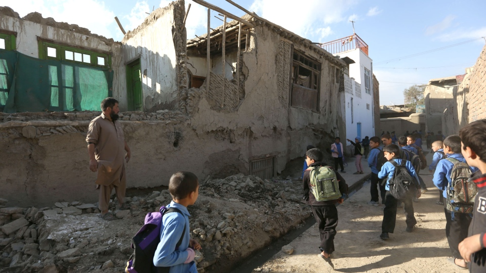 Afghan school boys walk to look a damaged house following a powerful earthquake that could be felt across South Asia, in Kabul, Afghanistan, Monday, Oct. 26, 2015. (AP / Rahmat Gul)