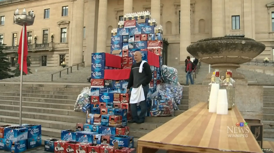 Angelo Mondragon, president of the Manitoba Rural Hotel Association, stands with the beer-box throne erected on the steps on the Manitoba legislature on Oct. 26.