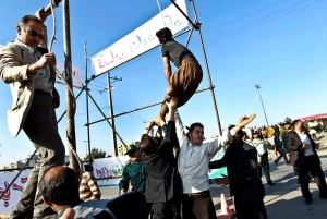 Men hold a man hanged in public, to prevent his execution, after he was pardoned by the family of the policeman he was convicted of killing, in Mashhad, northeastern Iran on May 8, 2013. (AP / Mehdi Bolourian)