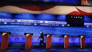 A crew member walks past the candidate podiums at the venue for the Oct. 28 CNBC Republican presidential debate, inside the Coors Events Center at the University of Colorado in Boulder, Colo. on Tuesday, Oct. 27, 2015. (AP / Brennan Linsley)