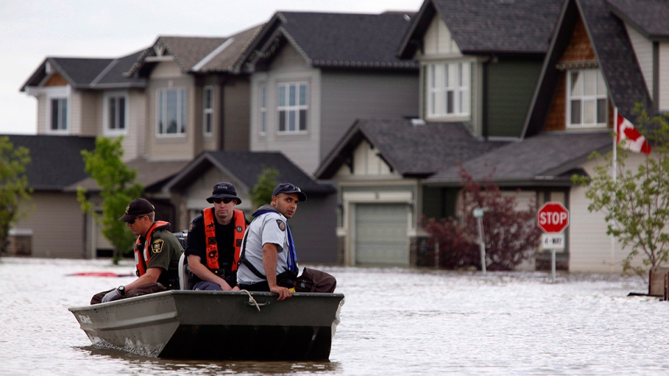 Members of the RCMP return from a boat patrol of a flooded neighborhood in High River, Alta., on July 4, 2013. (Jeff McIntosh / THE CANADIAN PRESS)