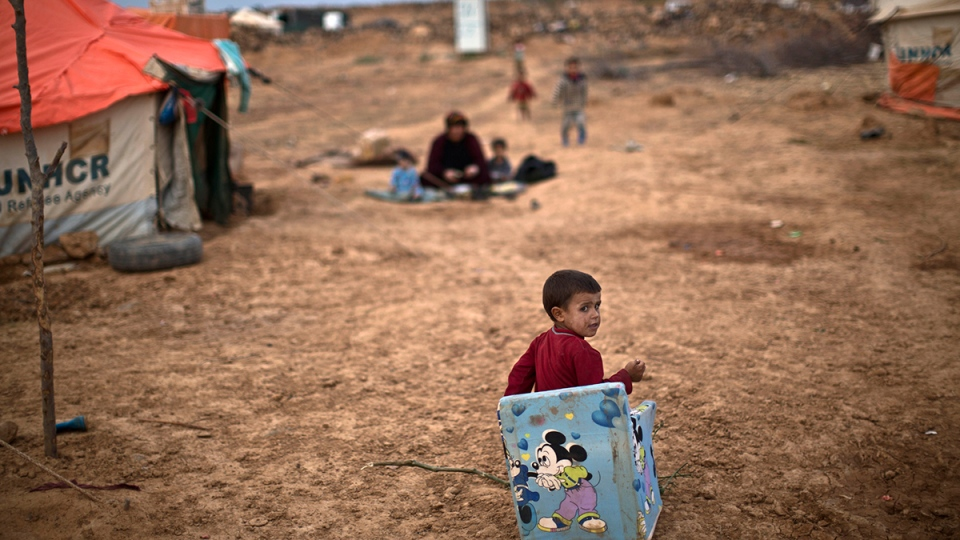 Syrian refugee boy Ahmad Faleh, 3, plays outside his family's tent at an informal settlement near the Syrian border on the outskirts of Mafraq, Jordan, Wednesday, Oct. 28, 2015. (AP Photo/Muhammed Muheisen)