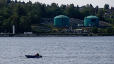 Two men fishing for crab sit on a boat on the waters of Burrard Inlet in North Vancouver as the Kinder Morgan Burnaby Terminal is seen in the distance in Burnaby, B.C., on Friday May 2, 2014. (THE CANADIAN PRESS/Darryl Dyck)