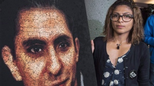Ensaf Haidar stands next to a poster of a book of articles written by the imprisoned Saudi blogger and Haidar's husband, Raif Badawi, on June 16, 2015 in Montreal. (Paul Chiasson / THE CANADIAN PRESS)