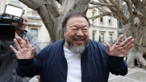 In this Tuesday, Sept. 15, 2015 file photo Chinese artist Ai Weiwei poses for photographers with one of his pieces at his exhibition at the Royal Academy of Arts in London. (AP / Frank Augstein, File)