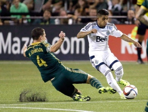 Portland Timbers midfielder Will Johnson, left, slides in on Vancouver Whitecaps midfielder Cristian Techera during the second half of an MLS soccer game in Portland, Ore., on July 18, 2015. (Don Ryan/THE CANADIAN PRESS/AP)