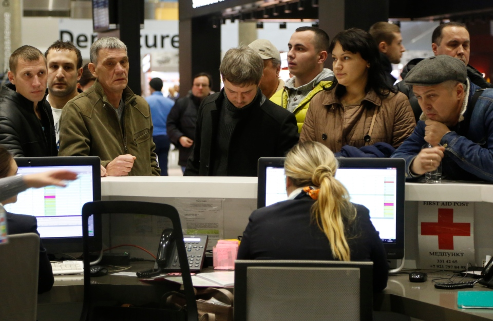 People gather at the airline information desk at of Russian airline Kogalymavia's desk at Pulkovo airport in St. Petersburg, Russia, Saturday, Oct. 31, 2015, after a Russian airliner with 217 passengers and seven crew aboard crashed.  (AP Photo/Dmitry Lovetsky)