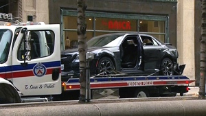 A vehicle that crashed into a building after fleeing a shooting downtown Toronto is seen being towed away, Saturday, Oct. 31, 2015.