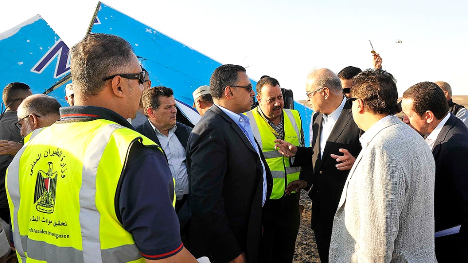 Egypt's Prime Minister Sherif Ismail and military and government officials visit the site where a Russian passenger plane carrying 224 people crashed in Hassana, Egypt, Friday, Oct. 31, 2015. (Suliman el-Oteify / Egypt Prime Minister's Office)