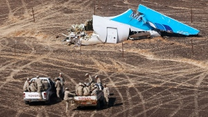 Egyptian Military on cars approach a plane's tail at the wreckage of a passenger jet bound for St. Petersburg in Russia that crashed in Hassana, Egypt, on Sunday, Nov. 1, 2015. (Maxim Grigoriev / Russian Ministry for Emergency Situations)