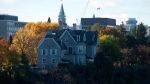 The prime ministers' residence, 24 Sussex, is seen on the banks of the Ottawa River in Ottawa on Monday, Oct. 26, 2015. The Parliament Hill Peace Tower is in the distance. (Sean Kilpatrick / THE CANADIAN PRESS)