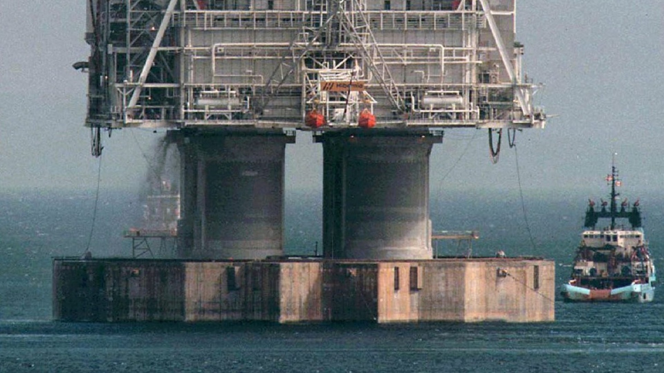 A tug positions itself near the base of the Hibernia platform in Bull Arm, Trinity Bay, Nfld., on Thursday, May 22, 1997 (The Canadian Press/Jonathan Hayward)