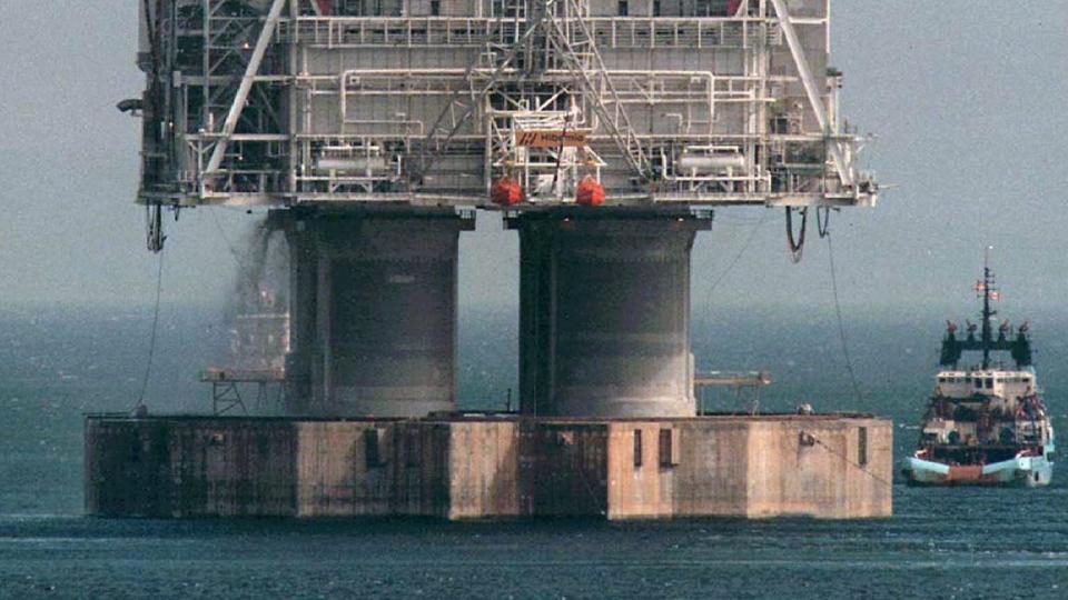 A tug positions itself near the base of the Hibernia platform in Bull Arm, Trinity Bay, Nfld., on Thursday, May 22, 1997 (Jonathan Hayward/The Canadian Press)