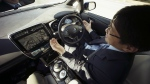 Nissan Motor Co. General Manager Tetsuya Iijima drives a self-driving prototype vehicle during a test drive in Tokyo on Tuesday, Nov. 3, 2015. (AP / Eugene Hoshiko)