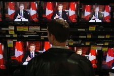 A shopper watches as Prime Minister Stephen Harper addresses the country on television screens at an electronics store in Vancouver, B.C., on Wednesday December 3, 2008. (Darryl Dyck / THE CANADIAN PRESS)