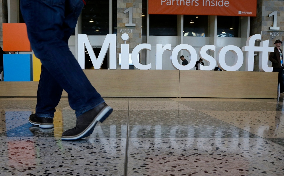 A man walks past a Microsoft sign set up for the Microsoft BUILD conference at Moscone Center in San Francisco on April 28, 2015. (AP / Jeff Chiu)