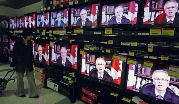 A shopper watches as Liberal Leader Stephane Dion is seen on television screens at an electronics store in Vancouver B.C., on Wednesday, Dec. 3, 2008. (Darryl Dyck / THE CANADIAN PRESS)