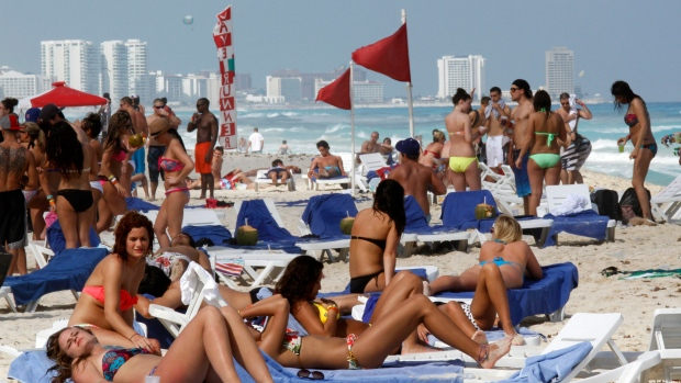 FILE - People hang out during spring break in Cancun, Mexico, on March 10, 2012. (AP Photo/Israel Leal)