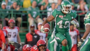 Saskatchewan Roughriders linebacker Jeff Knox Jr. (49) runs after an interception as Calgary Stampeders wide receiver Eric Rogers (80) fails to make the tackle during pre-season CFL action in Regina on Friday June 19, 2015. (THE CANADIAN PRESS/Derek Mortensen)