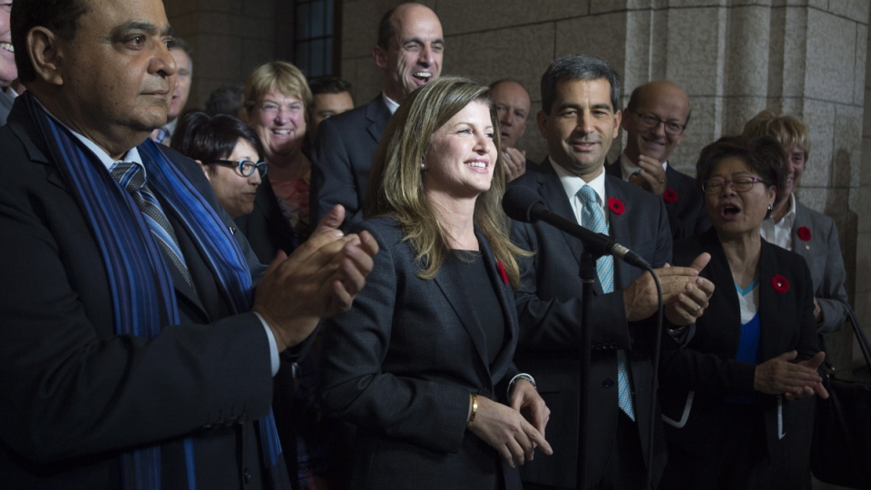 Surrounded by members of caucus, Rona Ambrose speaks after being named as the interim-leader of the Conservative party following a caucus meeting, in Ottawa, Thursday, Nov. 5, 2015. (Adrian Wyld / THE CANADIAN PRESS)