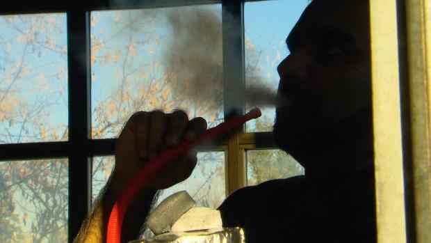 Man smoking hookah pipe in a hookah lounge.