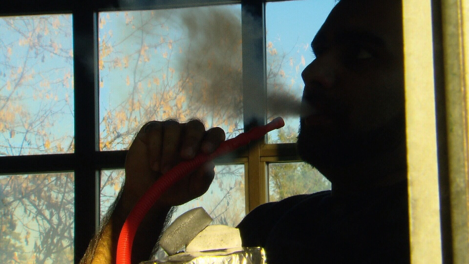 Man smoking hookah pipe in a hookah lounge.