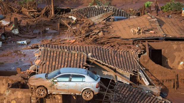 A car and two dogs are seen on the roof of destroyed houses at the small town of Bento Rodrigues after a dam burst on Thursday in Minas Gerais state, Brazil, Friday, Nov. 6, 2015. (AP / Felipe Dana)  <br><br> Brazilian rescuers searched feverishly Friday for possible survivors after two dams burst at an iron ore mine in a southeastern mountainous area