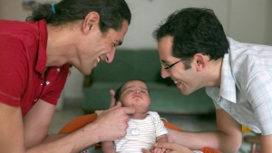 Yonatan Gher, right, and his partner Omer Gher play with their month-old son Evyatar Gher on Sunday, Nov. 16, 2008. Evyatar, which means more fathers in Hebrew, was conceived with a Mumbai-based surrogate mother with sperm donated by Yonatan. (AP Photo/Hindustan Times, Manoj Patil)