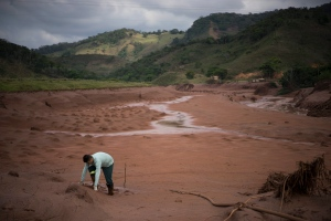 An electricity worker attempts to cross a flooded area in Barra Longa after a dam burst in Minas Gerais state on Saturday, Nov. 7, 2015. (AP / Felipe Dana)
