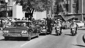 "In this Nov. 22, 1963 file photo, seen through the foreground convertible's windshield, President John F. Kennedy's hand reaches toward his head within seconds of being fatally shot as the motorcade proceeds along Elm Street past the Texas School Book Depository in Dallas.(AP Photo/James W. ""Ike"" Altgens, File)"