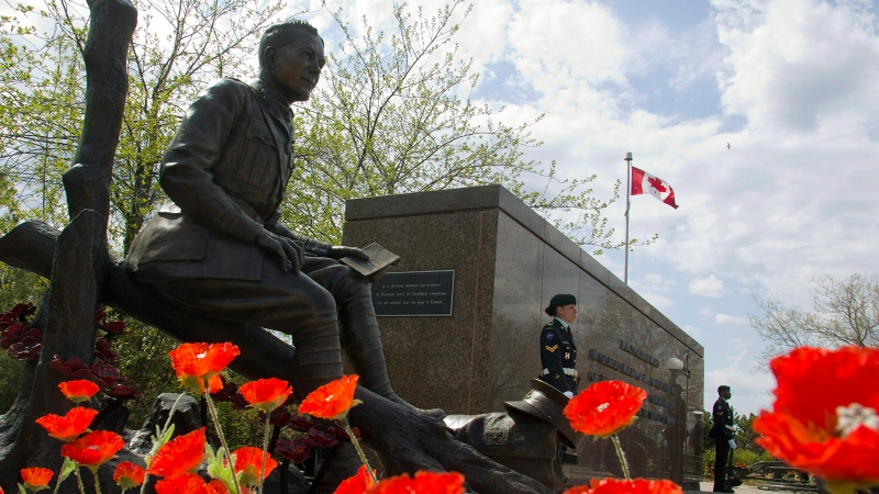 Poppies surround the newly unveiled statue of Lt.-Col. John McCrae to commemorate the Second Battle of Ypres and his poem 'In Flanders Fields,' during a ceremony in Ottawa on Sunday, May 3, 2015. (Fred Chartrand / THE CANADIAN PRESS)