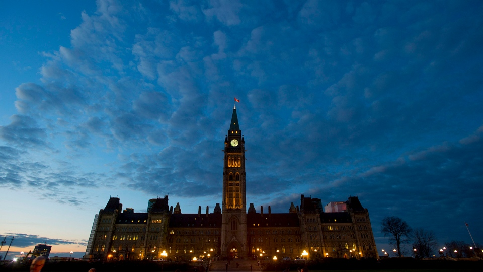 The sun sets behind Parliament Hill in Ottawa on Thursday, November 5, 2015. (Sean Kilpatrick / THE CANADIAN PRESS)