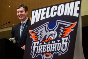 Flint, Mich., Mayor Dayne Walling speaks during a press conference introducing the city's new Ontario Hockey League hockey, the Flint Firebirds, Monday, March 16, 2015, at Perani Arena in Flint, Mich. (AP /The Flint Journal-MLive.com, Jake May)