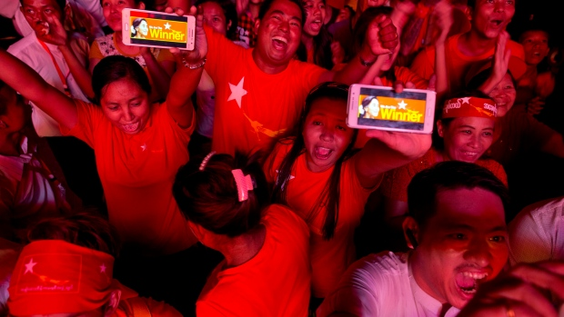 Supporters of Burma's National League for Democracy party display their mobile phone with a pictures of Suu Kyi as they gather to celebrate unofficial election results outside the NLD headquarters in Yangon, Burma, Monday, Nov. 9, 2015. (AP / Gemunu Amarasinghe)