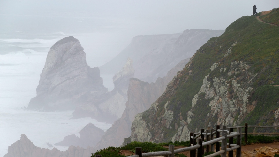 A tourist enjoys the view from the cliffs of Cabo da Roca, Cape Roca, the westernmost point of continental Europe, north west of Lisbon, Wednesday, Jan. 5 2014. (AP Photo/Armando Franca)
