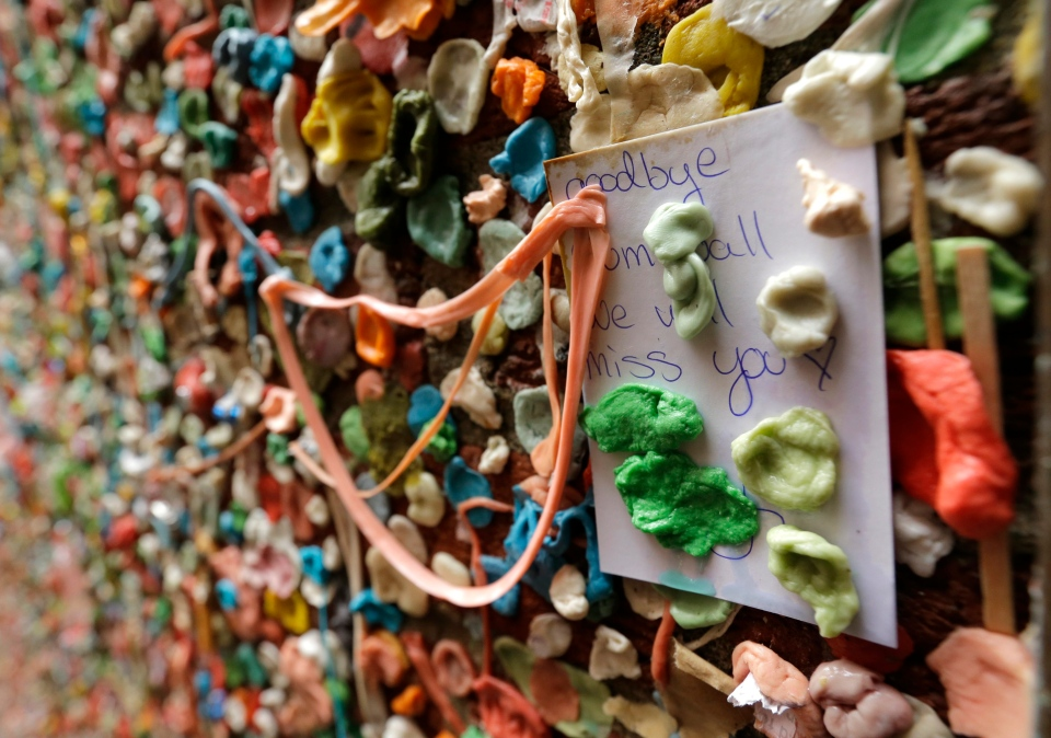 "A note that reads ""Goodbye gum wall, we will miss you,"" sticks to a wall partially obscured by gum on Nov. 9, 2015, at Seattle's ""gum wall"" at Pike Place Market. (Ted S. Warren / AP Photo)"