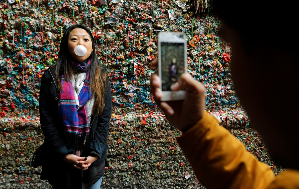 "Jessica Wang, left, visiting from Los Angeles, has her photo taken by Michael Teylan, right, at Seattle's ""gum wall"" at Pike Place Market on Nov. 9, 2015. (Ted S. Warren / AP Photo)"