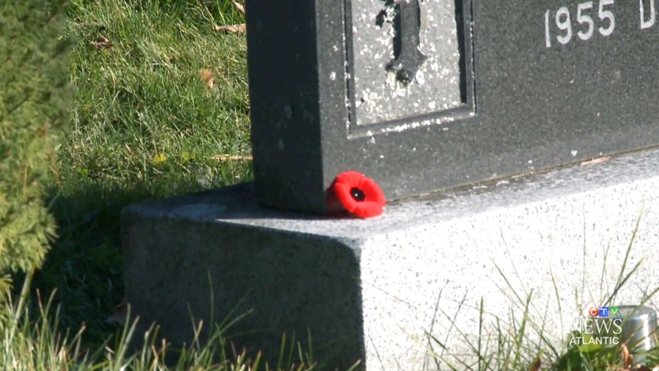 A poppy lays on the corner of a war veteran's grave in Oromocto, N.B.