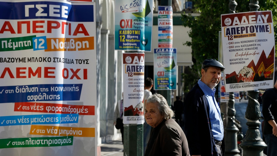 An elderly woman begs next to banners announcing tomorrow's general strike in Athens, Wednesday, Nov. 11, 2015. (AP / Thanassis Stavrakis)