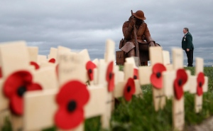 Larry Roberts, 60, a veteran from South Shields in England, who served with the Royal Green Jackets, stands for a moment looking at the sculpture entitled Eleven 'O' One in Seaham, County Durham, England, ahead of playing the bugle during a ceremony to mark Armistice Day, the anniversary of the end of the First World War, Wednesday Nov. 11, 2015. (Owen Humphreys / PA via AP)