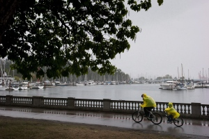A man reaches to pull up the hood on a poncho as he and a child ride a tandem bike along the Stanley Park seawall during a rain storm in Vancouver, B.C. on Aug. 29, 2015. (Darryl Dyck / THE CANADIAN PRESS)