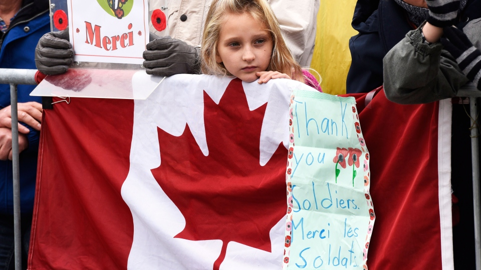 A young girl holds a sign of thanks for soldiers at the Remembrance Day ceremony at the National War Memorial in Ottawa, on Wednesday, Nov. 11, 2015. (Justin Tang / THE CANADIAN PRESS)