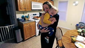 Cancer survivor Christine Ells embraces her twenty-month-old son Jameson after arriving home from work in Whitman, Mass., Monday, Nov. 9, 2015. (AP Photo/Charles Krupa)